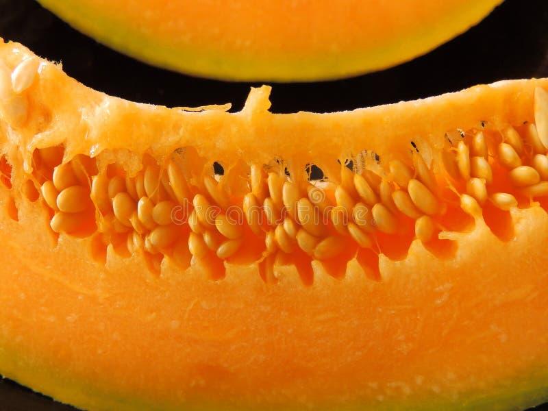 Pomarańczowy melonowy plasterek na czarnym tle obrazy royalty free