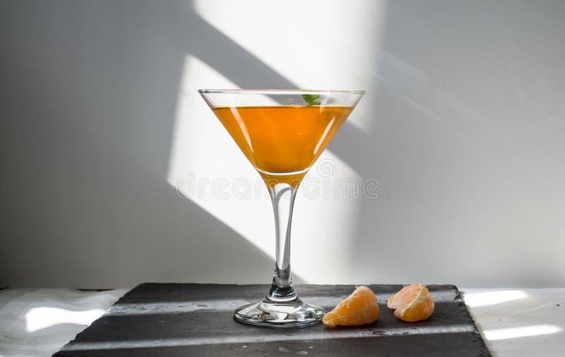 Pomarańczowy napój z zielenią opuszcza w szkle fotografia stock