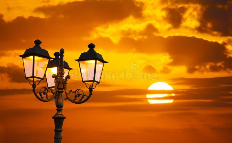 Pomarańczowy niebo z olśniewającym słońcem i lamppost zdjęcie royalty free