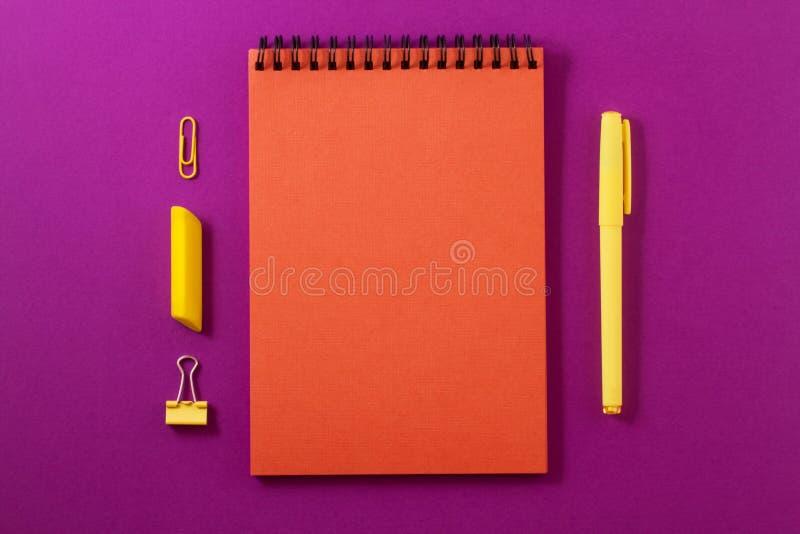 Pomarańczowy notatnik na jaskrawym purpurowym tle fotografia royalty free