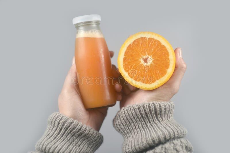 Pomarańczowy połówki cięcie, sok pomarańczowy na kobiet rękach z pulowerem na świetle i - szary tło Horyzontalny wizerunek zdjęcie royalty free