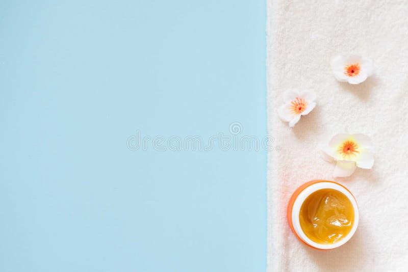 Pomarańczowy słój śmietanka i kwiaty na białym ręczniku na błękitnym tle, odgórny widok Fachowi kosmetyczni produkty obraz stock