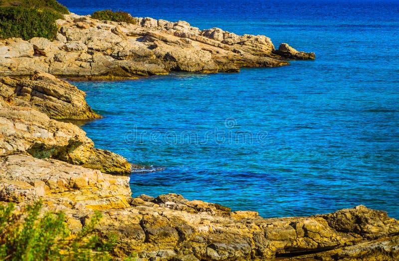 Pomarańczowy skalisty brzeg i piękny lazurowy błękitny morze obrazy royalty free