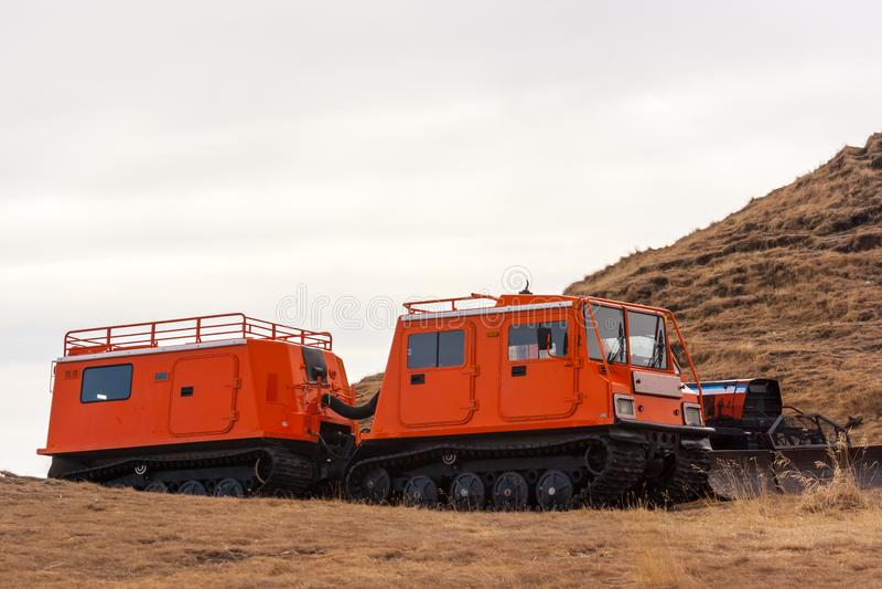 Pomarańczowy snowcat z drugi furgonem Inny pojazd z snowplow fotografia stock