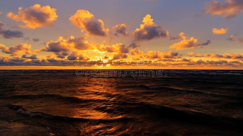 Pomarańczowy zmierzch nad morze bałtyckie linią brzegową z chmurami i odbiciem w falach, selekcyjna ostrość zdjęcia stock