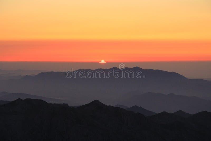 Pomarańczowy zmierzch z mgłą nad wysokimi górami obrazy royalty free