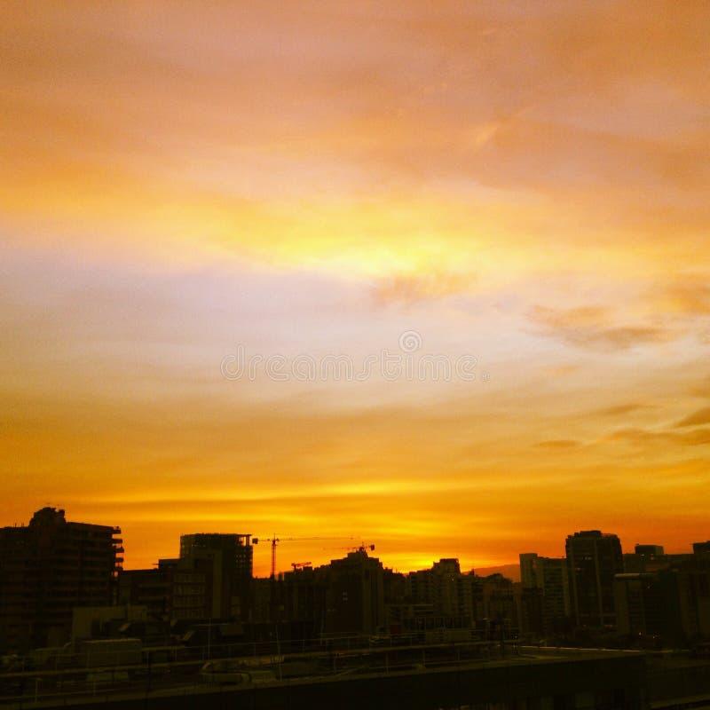 Pomarańczowy zmierzch z miastem czeka noc obraz stock