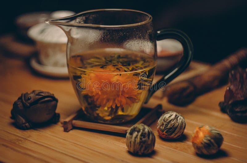 Pomarańczowi Petaled kwiaty w Jasnym Szklanym miotaczu Z wodą na Brown stołu zakończeniu W górę fotografii obraz stock