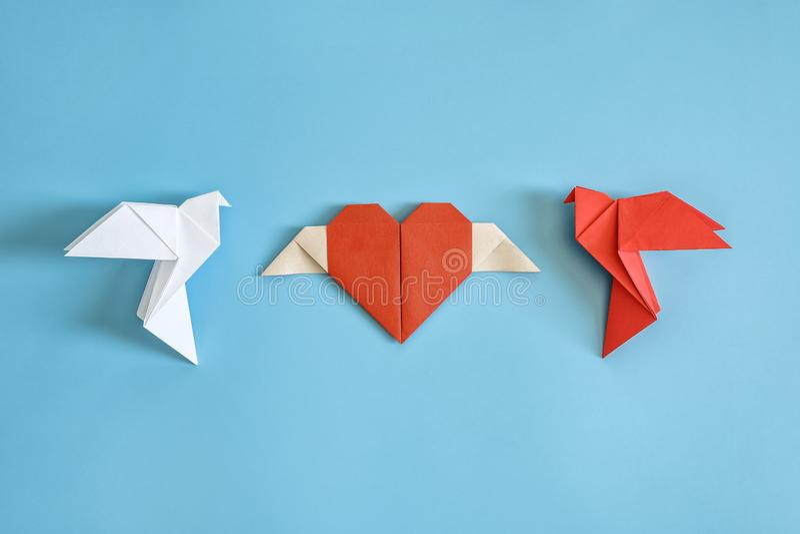 Pomba vermelha e branca do papel do orig?mi em um fundo azul e em um cora??o vermelho foto de stock royalty free