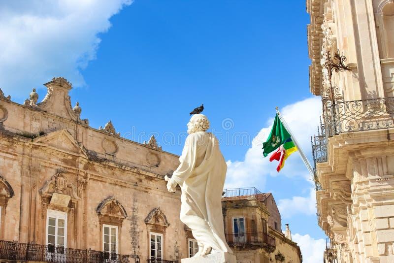 Pombo que senta-se em uma estátua histórica que pertence à catedral de Siracusa em Piazza Duomo em Siracusa, Sicília, Itália Pomb imagens de stock