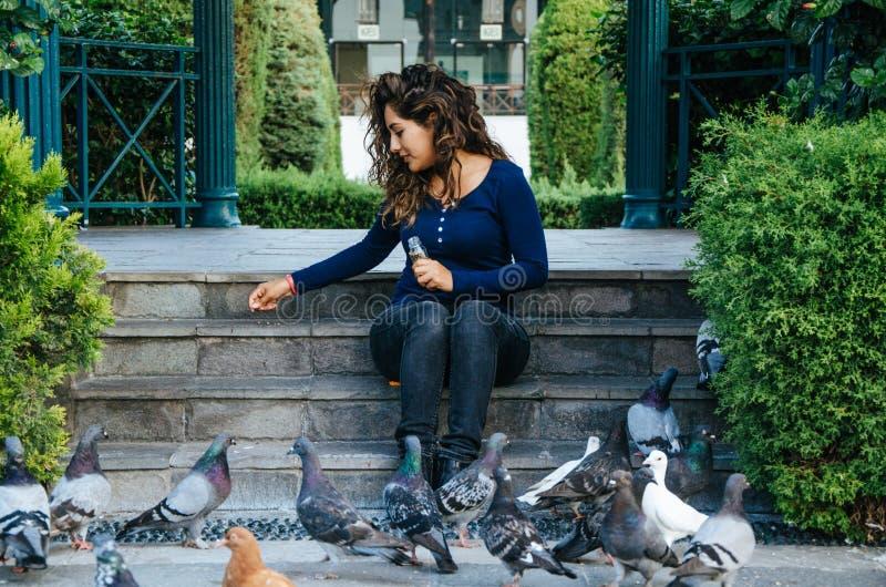 Pombos de alimentação de sorriso bonitos da mulher no parque durante o dia imagens de stock
