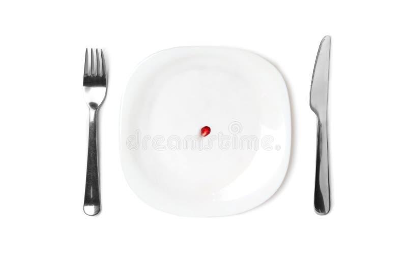 Pomegranaatzaad op een lege witte plaat Naast de plaat zijn messenmakerswerk Conceptueel: dieet en een kleine hoeveelheid voedsel royalty-vrije stock afbeeldingen