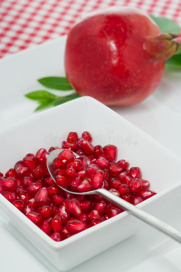 Pomegranate. And  seeds in a white bowl stock photo