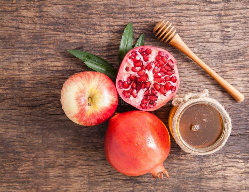 Pomegranate, apple and Honey for traditional holiday symbols Rosh hashanah royalty free stock photo