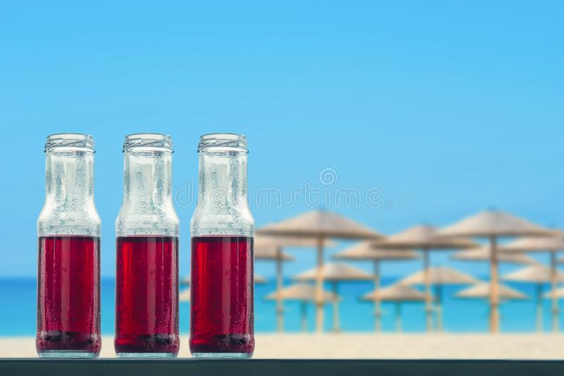 Pomegranate cold juice in bottles on the beach and straw umbrellas backgrounds royalty free stock image