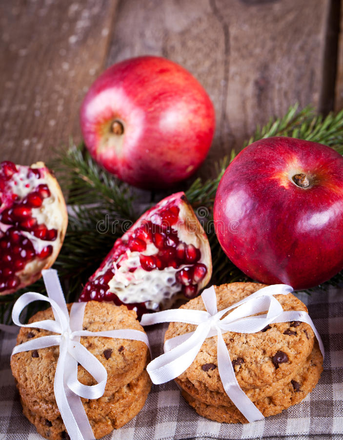 Pomegranate fruit, cookies and apples on wooden background stock images