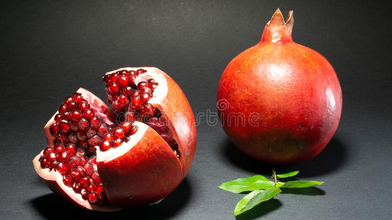 Pomegranate fruit, one foot is opened and you can see the grains near the second. Green foliage, the background is black, close-up stock photography