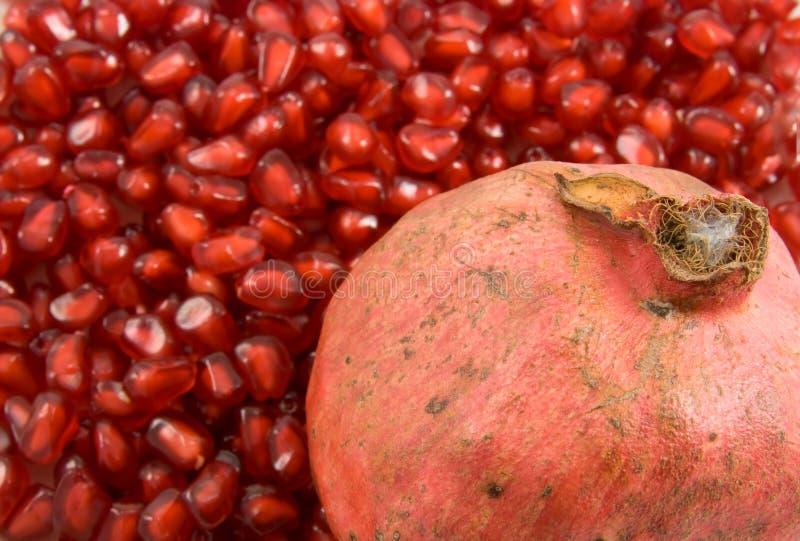 Pomegranate fruit on pomegranate seeds background. Ripe pomegranate fruit on pomegranate seeds background royalty free stock image