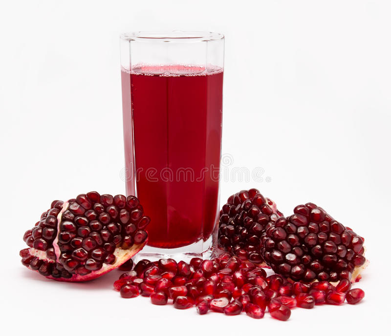Pomegranate juice in glass and pomegranates on white royalty free stock images