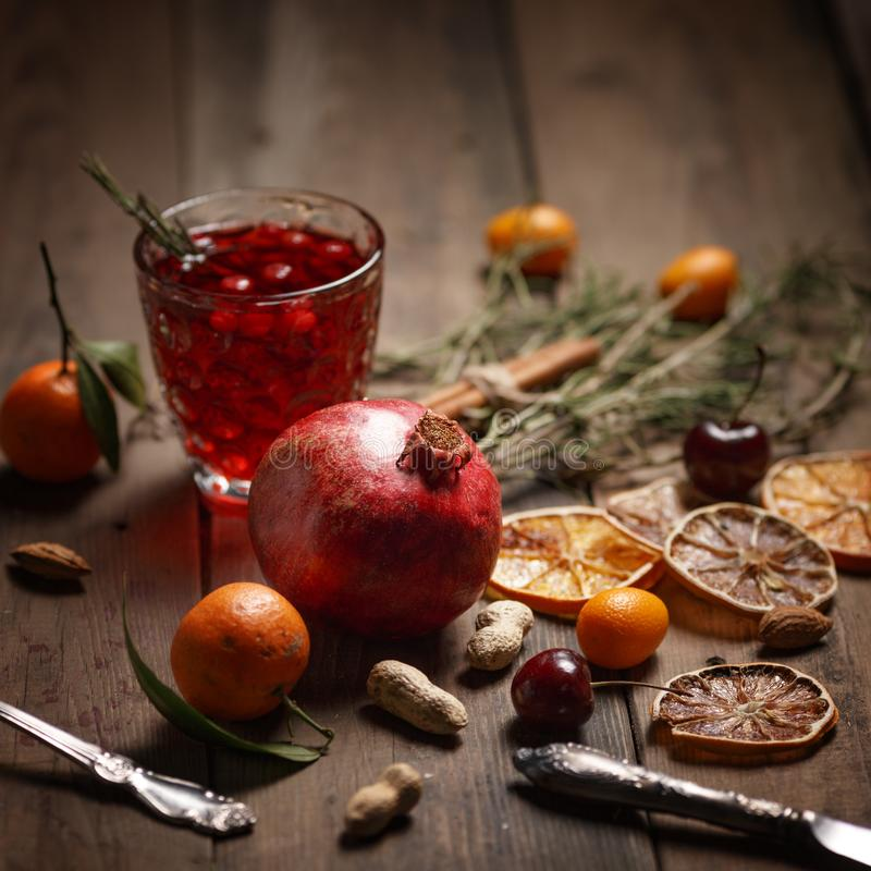 Pomegranate juice with pomegranates and dried fruits on a wooden table. Country style stock photo