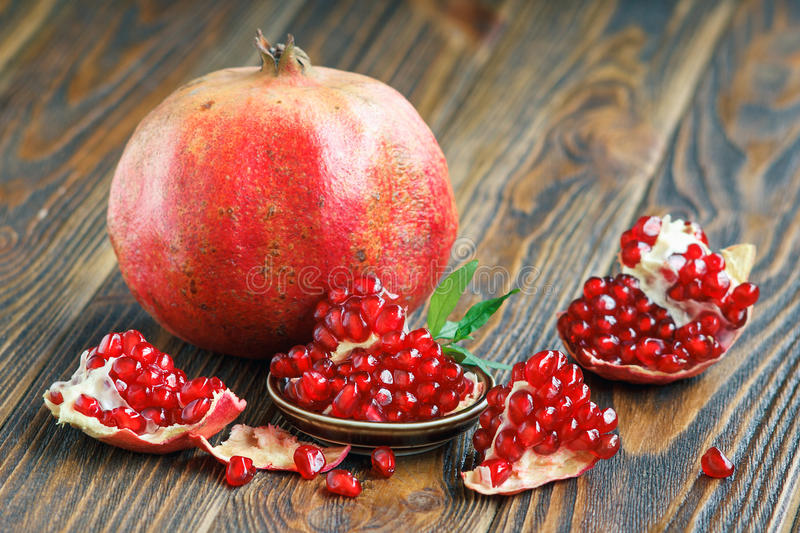Pomegranate juice with ripe fresh punica granatum fruits. Glass of pomegranate juice with ripe fresh punica granatum fruits with leaves on wooden table close-up royalty free stock photos