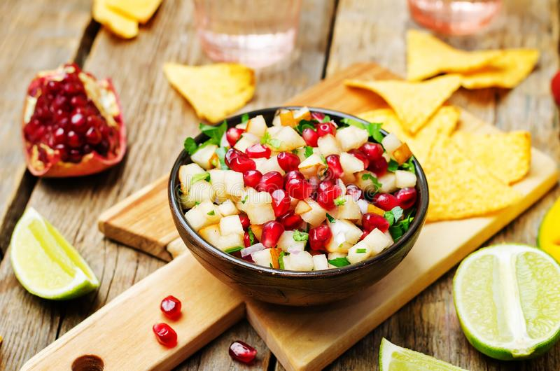 Pomegranate pear salsa on a dark wood background royalty free stock photo