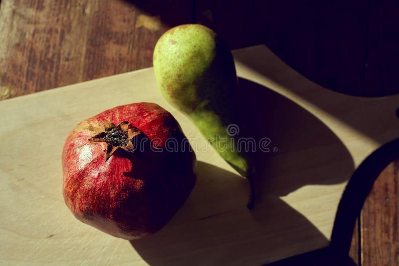 Pomegranate and pear on the table with the evening light and hard shadows. View from above royalty free stock images