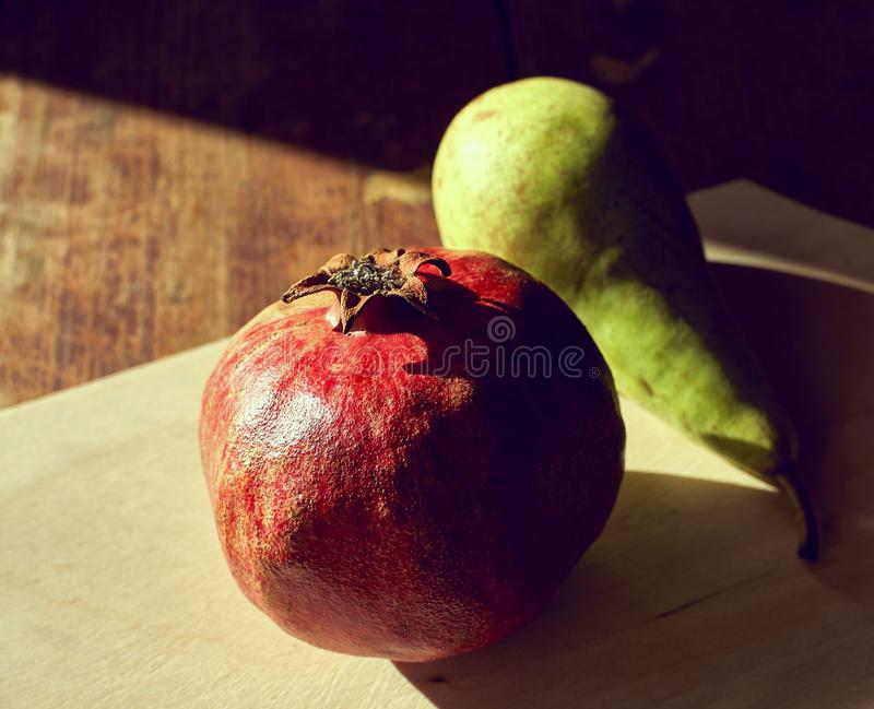 Pomegranate and pear on the table with the evening light and hard shadows. View from above stock photo