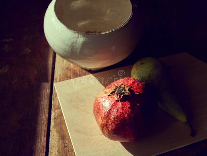 Pomegranate and pear on the table with the evening light and hard shadows. View from above royalty free stock photography