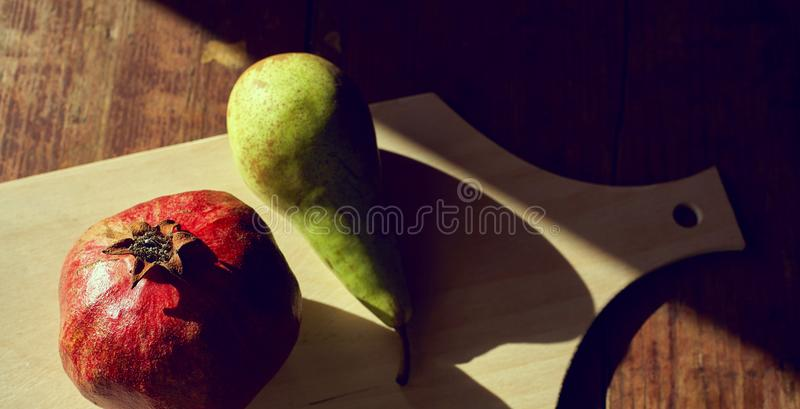 Pomegranate and pear on the table with the evening light and hard shadows. View from above stock photos