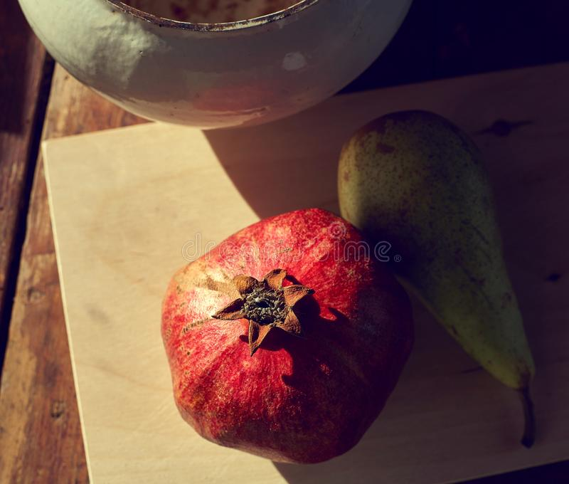 Pomegranate and pear on the table with the evening light and hard shadows. View from above royalty free stock image
