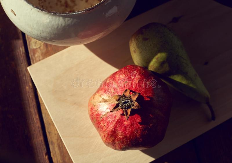 Pomegranate and pear on the table with the evening light and hard shadows. View from above stock images