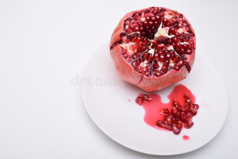 Pomegranate Punica granatum isolated on white background. Pomegranates are a source of many antioxidants, fibre, vitamins A, C, B. Pomegranate on plate Punica stock images