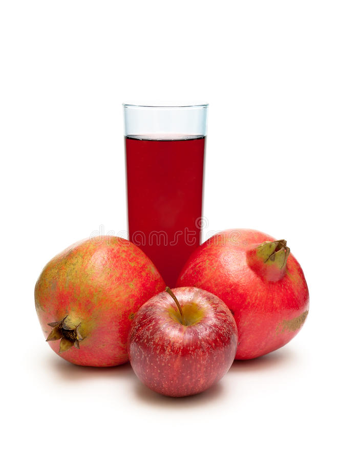 Pomegranate, red apple and a glass of juice on a white background. Vertical photo royalty free stock photography