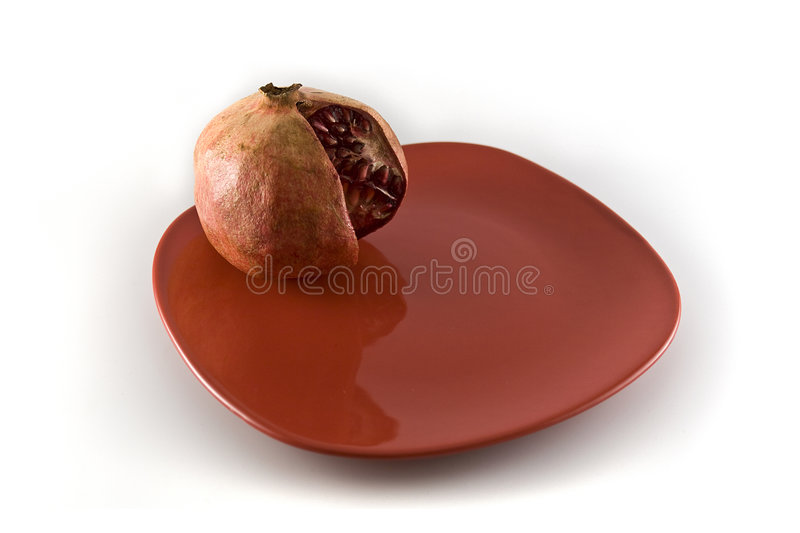 Pomegranate on the red plate royalty free stock photos