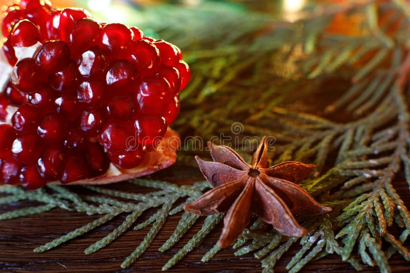 Pomegranate seeds and anise on a wooden table with colorful backlight. selective focus. Background for new year greeting card.  royalty free stock image