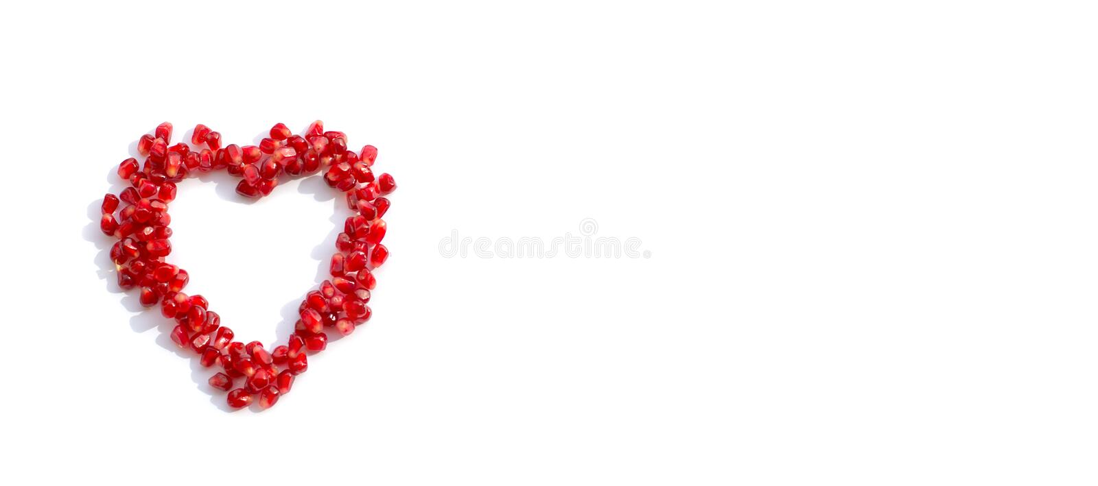 Pomegranate seeds scattered in the shape of a heart royalty free stock photos