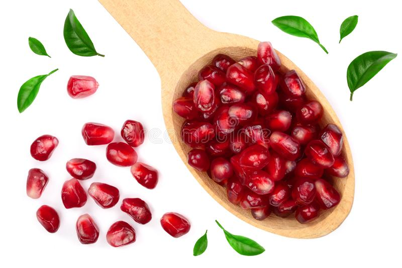 Pomegranate seeds in wooden spoon decorated with green leaves isolated on white background. Top view. Flat lay pattern stock photography