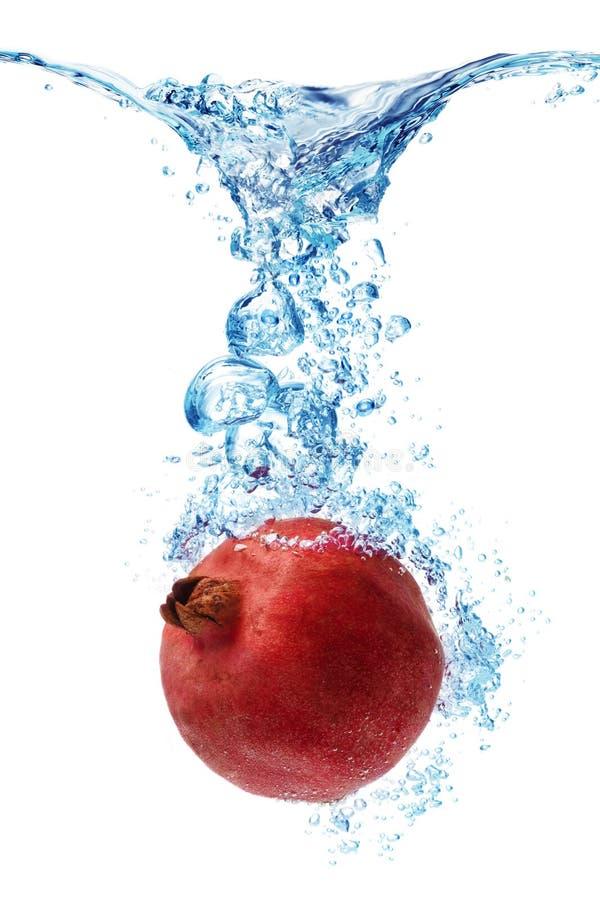 Pomegranate splashing in water royalty free stock photos