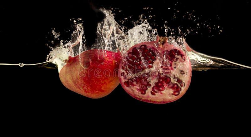Pomegranate splashing into water against black background. stock photo