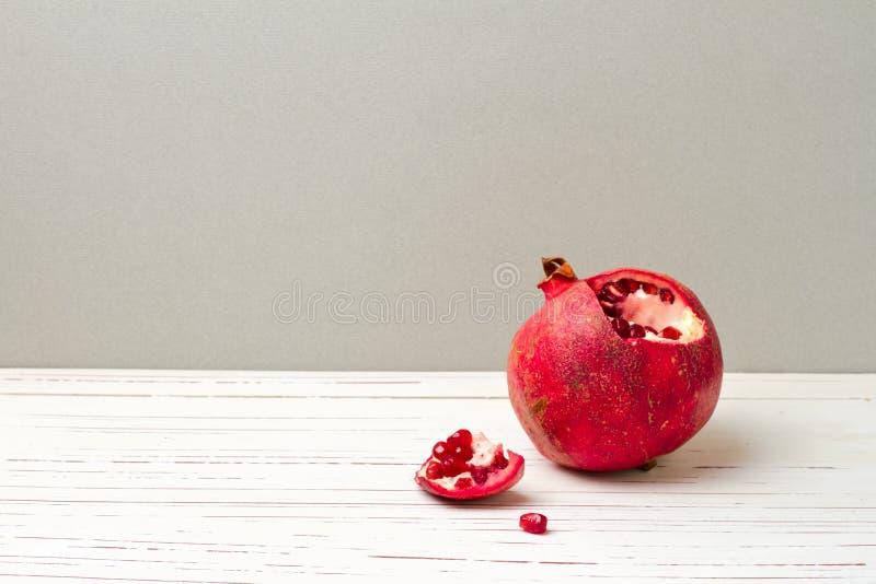 Pomegranate on white table stock photos