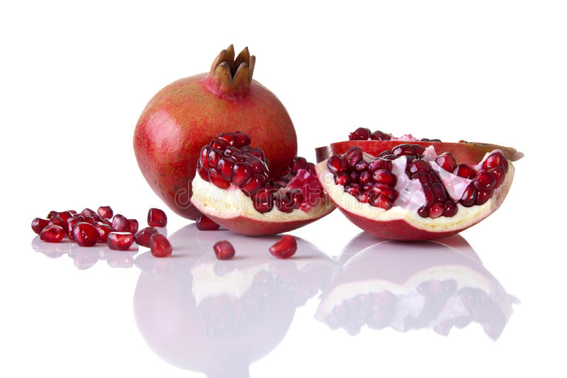 Pomegranate whole with halves and seeds royalty free stock image