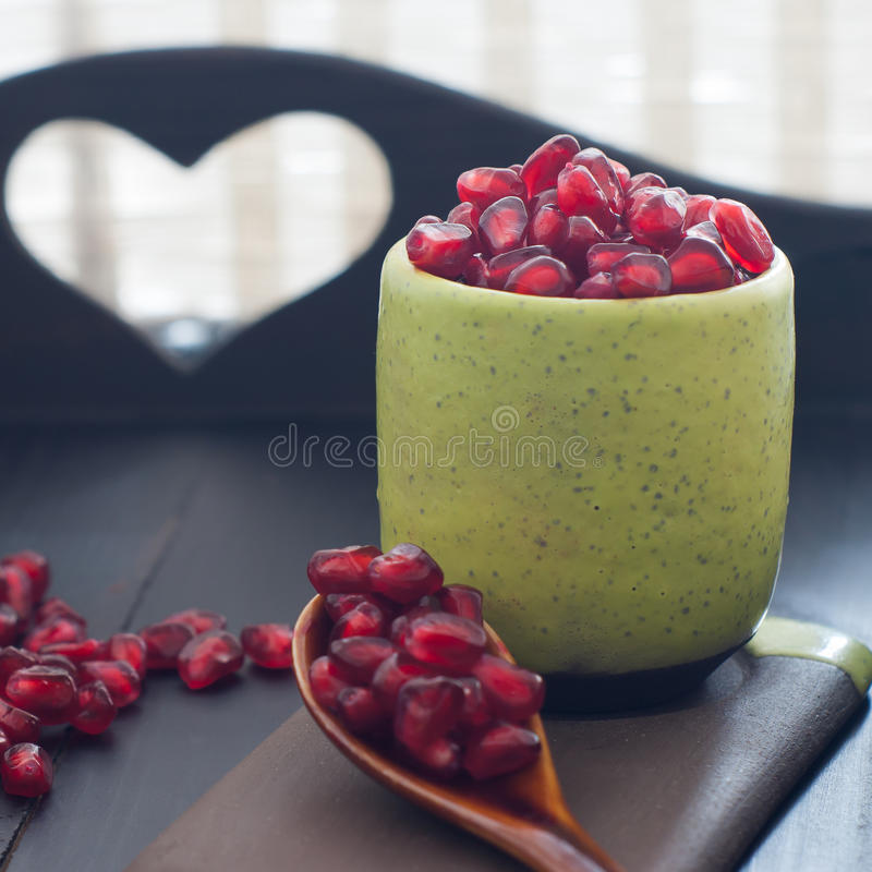 Pomegranatefrö portionr i grön krukmakeri royaltyfria bilder