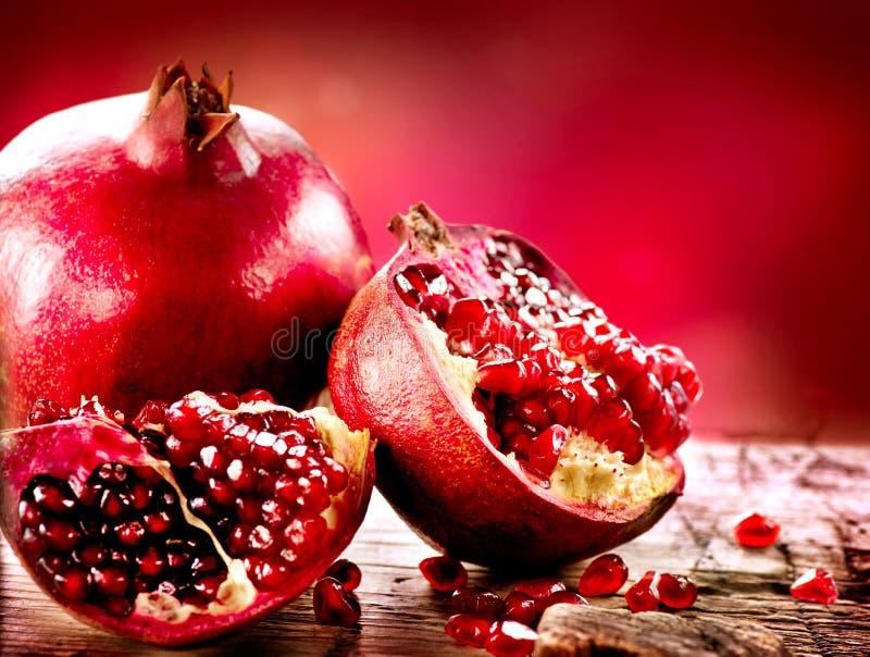 Pomegranates över röd bakgrund arkivbilder