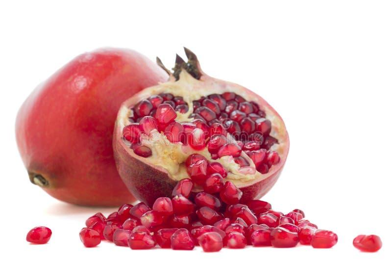 Pomegranates. Pomegranate and pomegranate seeds on white background royalty free stock photos