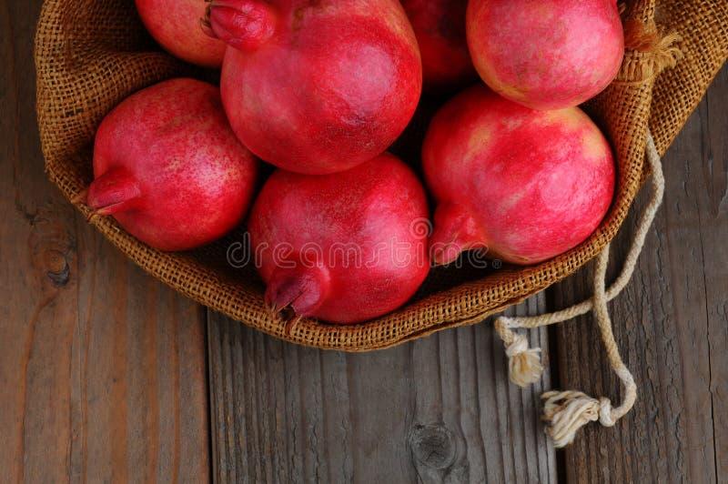 Pomegranates in Burlap Sack royalty free stock photos
