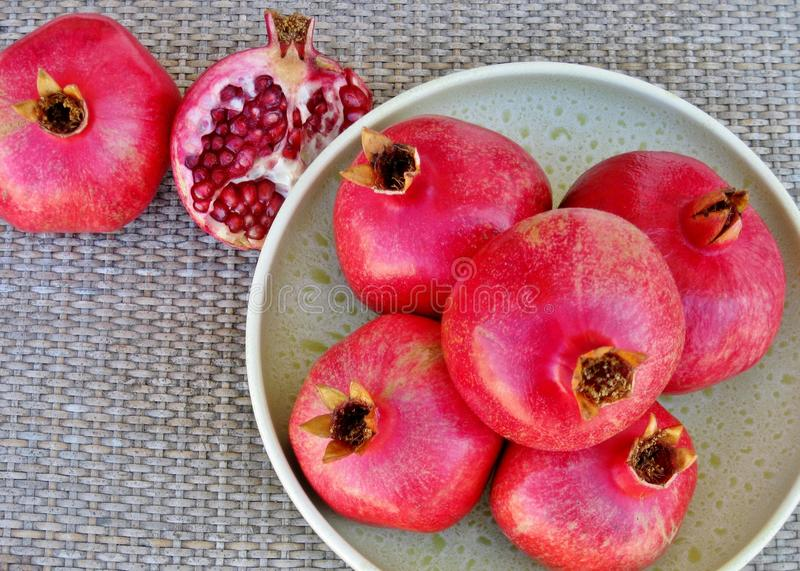 Ripe pomegranates in green vintage bowl on rustic rattan table royalty free stock image