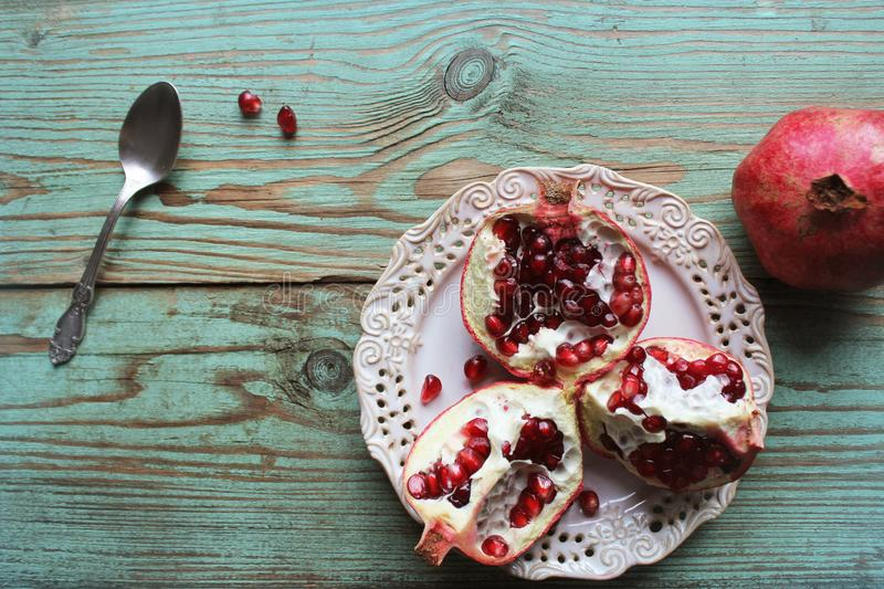 Pomegranates on white plate with spoon . Blue background . . royalty free stock photos
