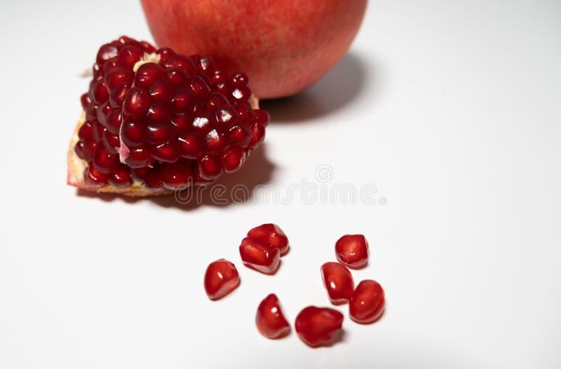 Pomegranatfrukt, spaltad med frön på vit bord arkivbilder