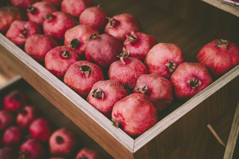 Pomegranatos vermelhos e suculentos na prateleira de madeira Colheita e venda de frutos frescos orgânicos imagens de stock